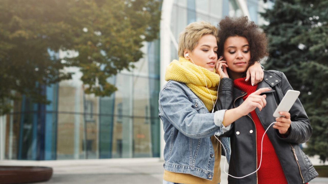 Happy multiethnic female friends listening to music on smartphone and sharing ear buds while having a city walk. Leisure, technology, friendship and urban lifestyle concept