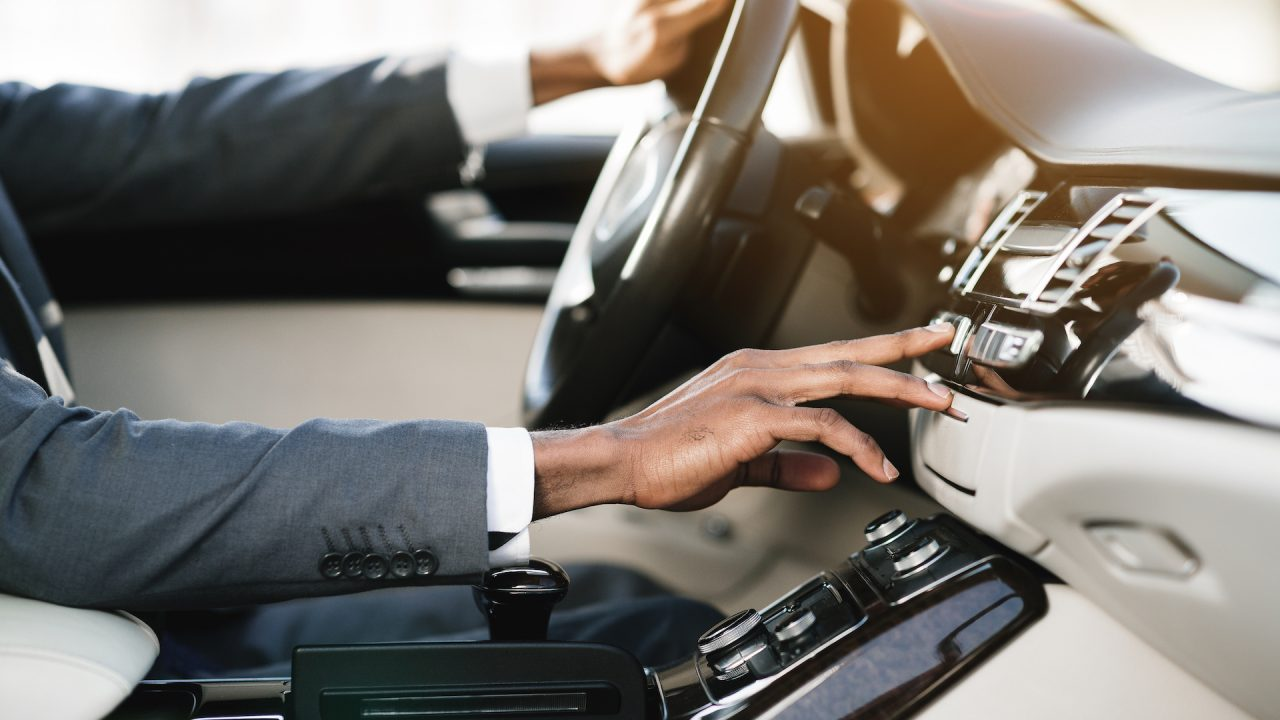 Young businessman changing radio stations driving in car during his morning commute to work